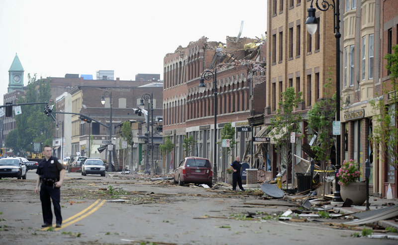 "Debris litters Main Street in Springfield, Mass., on Wednesday, after the top floor of a building on the street was shorn off by a tornado. One office worker reported a ""massive cloud of debris floating around in a circular, cylindrical fashion."""