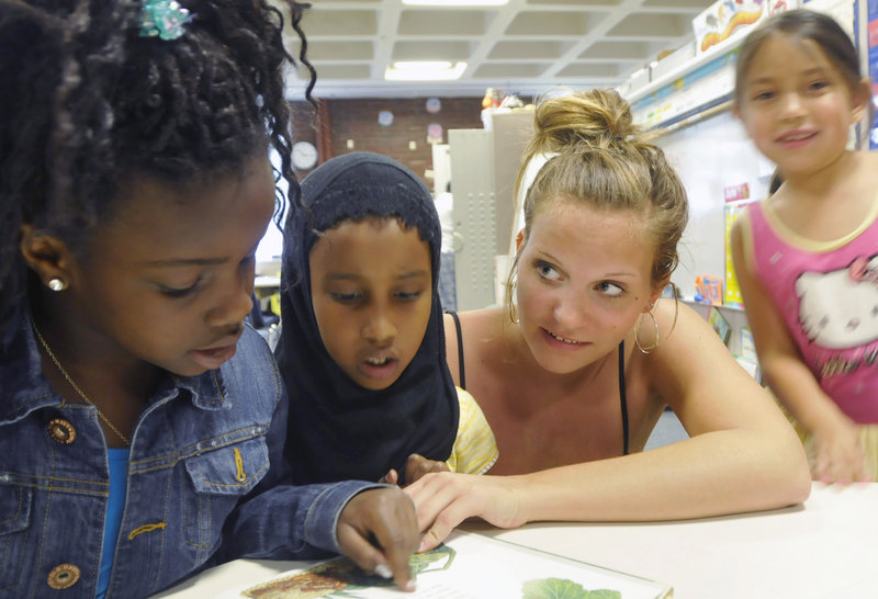 """Falmouth High School's Ellie MacEwan reads with Reiche Elementary School first-graders Sefora Kabala, left, and Mane Nour. """"I love interacting with the kids and I love listening to what they have to say about the world,"""" MacEwan said."""