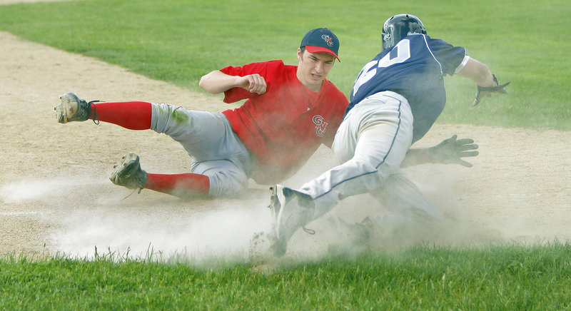 Devin Merritt of York dives back to third base Thursday after sliding past it, as Ryan Cavallaro of Gray-New Gloucester reaches for the ball. Merritt was safe because the ball got away. Gray-New Gloucester came away with a 7-4 victory at home.