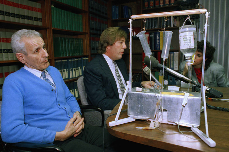 Dr. Jack Kevorkian, left, listens as his attorney, Geoffrey N. Fieger, talks with reporters with his suicide machine in the foreground of this 1991 photo. The assisted suicide advocate died Friday at the age of 83 at William Beaumont Hospital in Royal Oak, Mich., where he had been hospitalized since last month with pneumonia and kidney problems.
