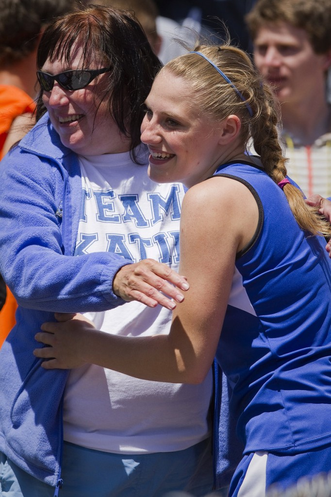 Katie Hatch of Old Orchard Beach gets a hug from her mom, Kim, after winning the 100-meter dash by .01 seconds in the Class C meet.