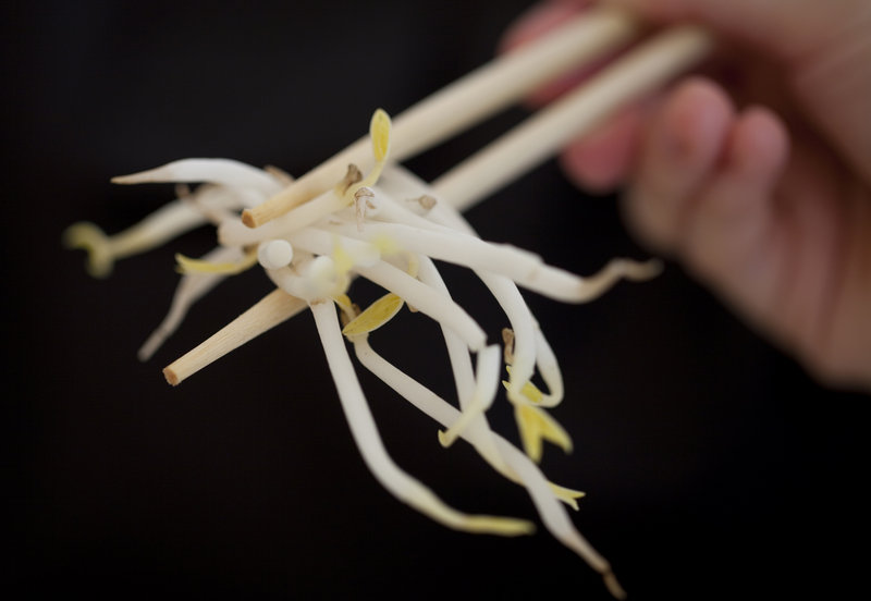 A woman holds sprouts with chopsticks in Germany Sunday. Sprouts are suspected in an E. coli outbreak that has killed 22.