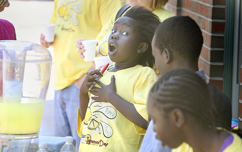 Akual Majok, 9, of Portland reacts to receiving a tip for good service at the Root Cellar's lemonade stand on Washington Avenue in Portland during Lemonade Day on Sunday.