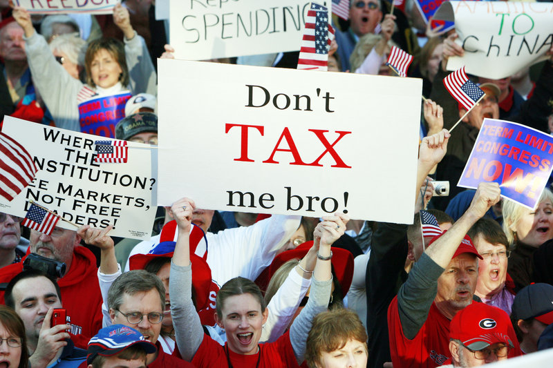 A woman holds a sign at a 2009 Atlanta Tea Party protest. Under strategist Grover Norquist's anti-tax pledge, raising revenue in any way requires an equal tax cut elsewhere to avoid expanding the size of government.