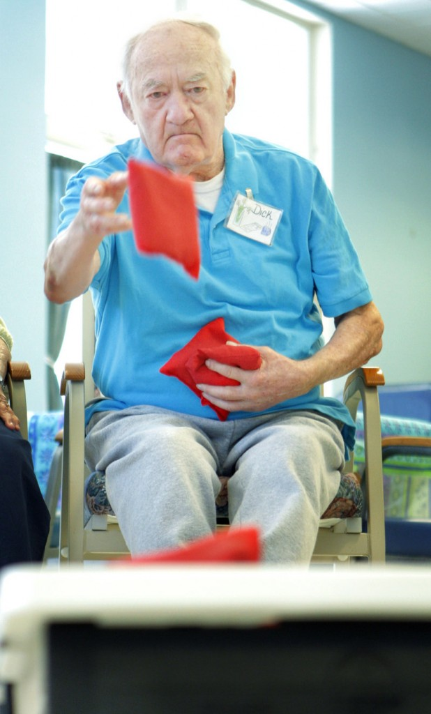 Dick Potvin throws a beanbag during an activity at the Truslow Adult Day Center in Saco on Monday.