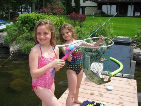 Aiyana, 10, and Dasey McNeill, 7, of Pittston show their first fish of the year, a 2 1⁄2 pound bass they caught at their grandmother Jackie McNeill's house on Togus Pond on Memorial Day.