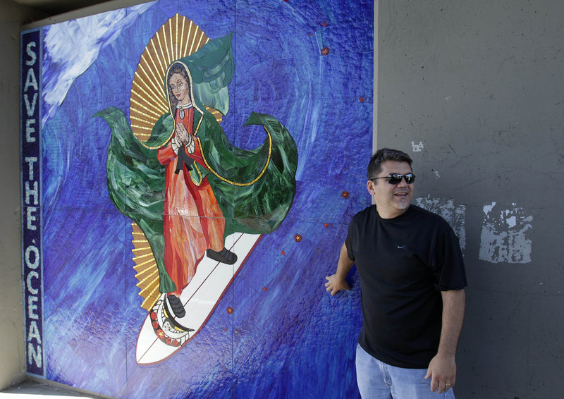 Nick Dinapoli of San Diego stands in front of an image of the Virgin of Guadalupe in Encinitas, Calif. Opinions vary, even among officials, on whether it must be removed.