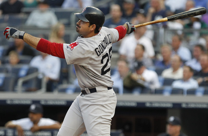 Boston's Adrian Gonzalez watches the flight of his RBI triple in the first inning Tuesday night at Yankees Stadium in New York. The Red Sox survived early wildness by starter Jon Lester to open their three-game series with a win.