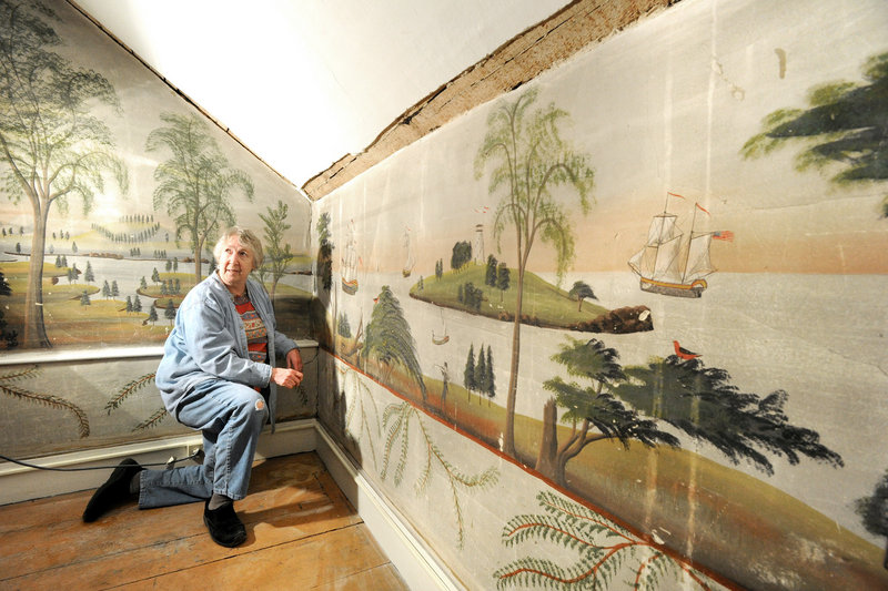 Jane Radcliffe, a board member of the Rufus Porter Museum, examines murals that are in the process of being moved from a home in East Baldwin to the new museum that is scheduled to open next year in Bridgton.