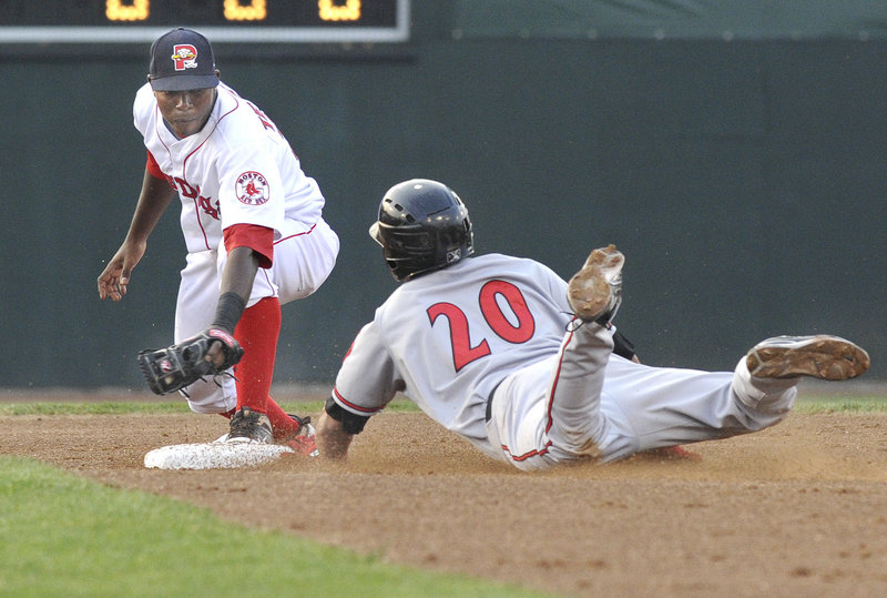 Portland's Oscar Tejeda slaps a tag on Richmond's Johnny Monell as he slides into an out that ended the top half of the second inning at Hadlock Field in Portland on Wednesday.