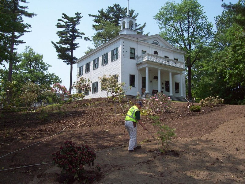 Cyndy Carroll, who works on the landscaping staff at USM Gorham, waters some of the plants at the Joe B. Parks Rhododendron Garden. The 1805 Academy Building, background, is part of the original campus at Gorham, and is now used by the art department.