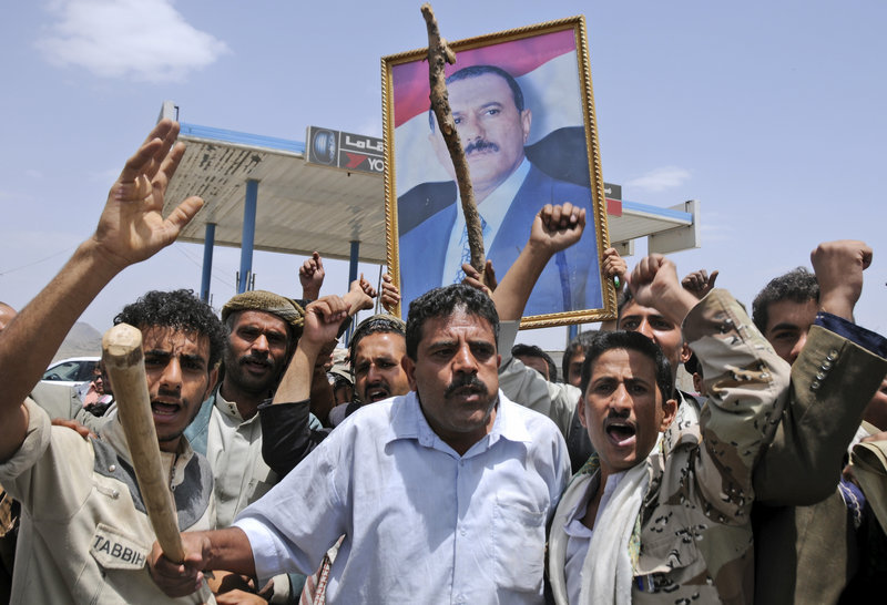 Supporters of Yemeni President Ali Abdullah Saleh hold up his portrait as they celebrate news that Saleh's health is stable after being taken to Saudi Arabia to receive treatment for wounds he suffered in a rocket attack on his compound.