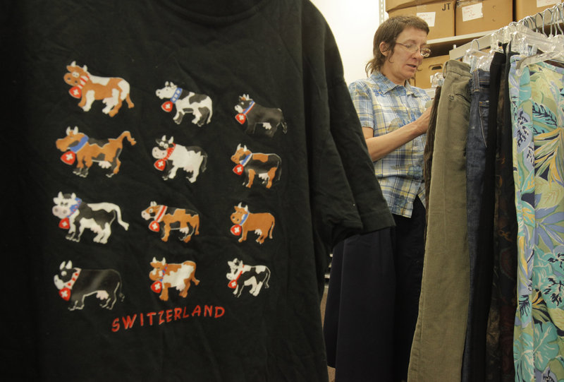Francine Spangler, a volunteer at the Catholic Charities Thrift Store in Union Station Plaza on St. John Street in Portland, prices pants Tuesday.