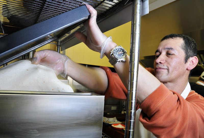 Manny Pena begins preparing an order at Taco Trio in South Portland.