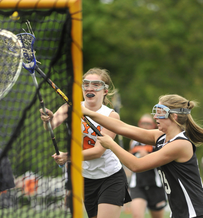 Katie Cawley of North Yarmouth Academy fires a shot on goal Saturday while defended by Paige Pillsbury of Gardiner during their Eastern Class B schoolgirl lacrosse semifinal at Yarmouth. NYA rolled to a 16-4 victory.