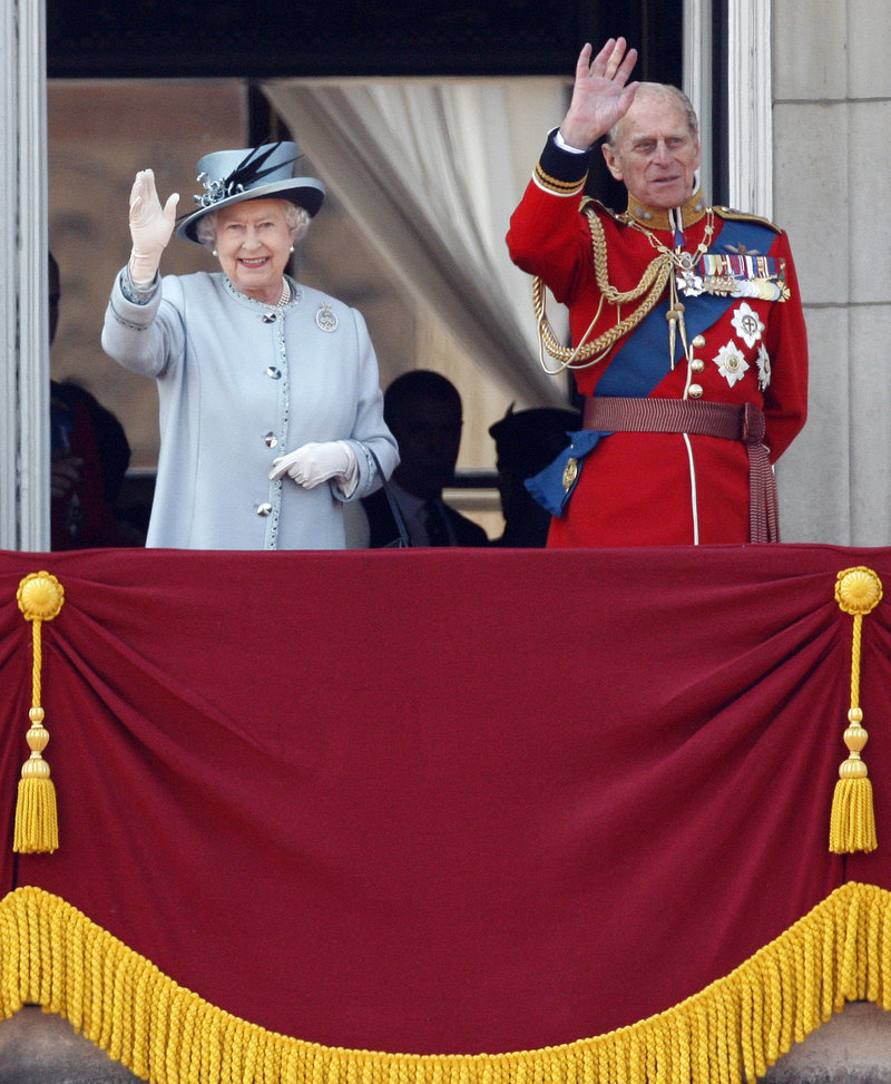 Queen Elizabeth II and Prince Philip wave from Buckingham Palace after returning from her official birthday ceremony in London on Saturday.