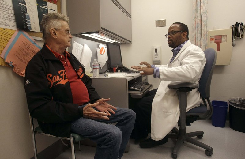 Randy Blach, left, talks to Dr. Malcolm John at the University of California, San Francisco's HIV clinic.