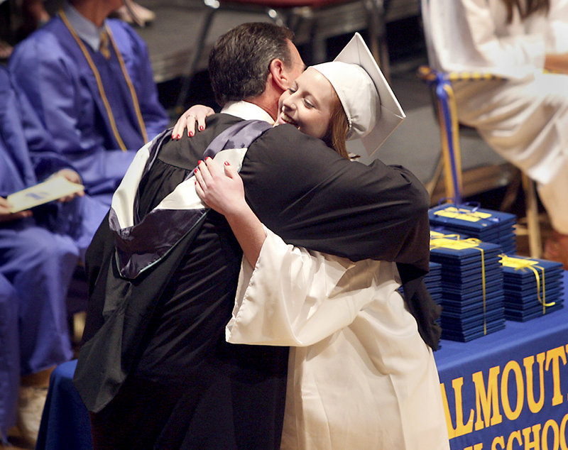 Lynzee Gillis receives a hug from Jack Hardy, Falmouth High School's assistant principal after receiving her diploma Sunday.