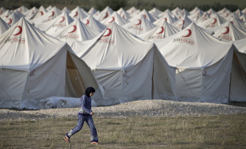 A Syrian woman walks in the new refugee tent compound in Boynuyogun, Turkey, near the Syrian border on Sunday. Syrian forces launched a crackdown on the town of Jisr al-Shughour, fueling fears that the clashes could spark a further influx of refugees into Turkey.