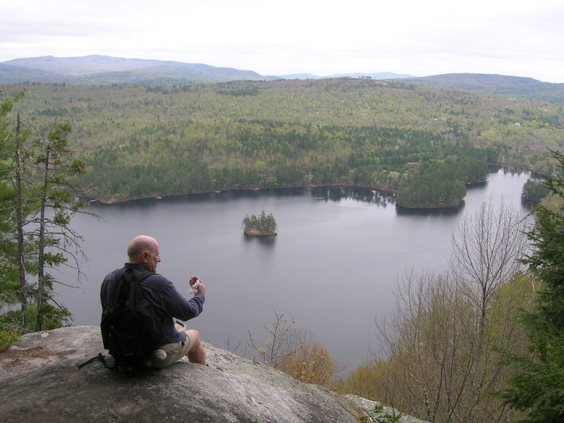 Blaine Mills of Greenwood takes a break overlooking Bryant Pond during a hike on Mount Christopher. A 2-mile loop treats hikers to several clifftop vistas.