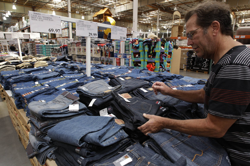 A shopper looks at inexpensive Levi jeans at a Costco in Mountain View, Calif., Monday. Because of the tepid economic recovery, Americans generally tend to be cautious about buying and search more diligently for deals when they do.