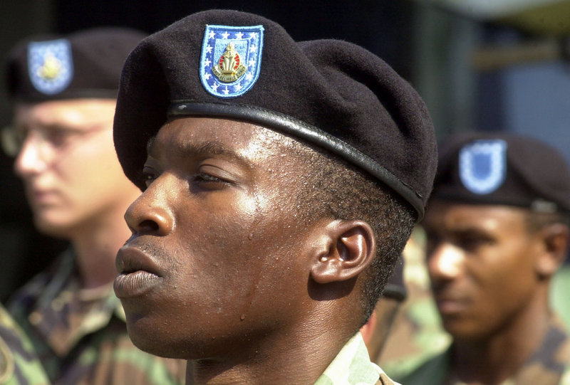 U.S. Army Sgt. Nathaniel Glover perspires from the heat as he stands in formation in Zamboanga, Philippines. Soldiers are gleeful that they can ditch the ill-fitting wool berets.