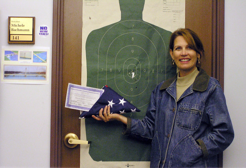 This 2005 photo provided by Michele Bachmann shows then-state Sen. Michele Bachmann as she poses with her state permit to carry a concealed weapon nestled in a folded U.S. flag at her office in the Minnesota Capitol in St. Paul. In Bachmann's quick rise from state lawmaker to unofficial tea party ambassador in Washington, her brazen style has kept Republican leaders on edge and appealed to those in the GOP searching for a fresh, unfettered voice.