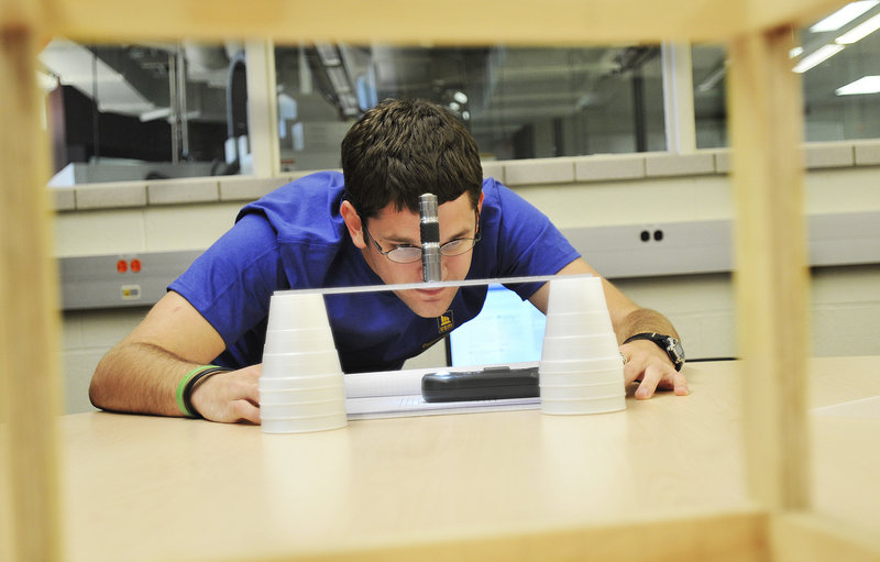 "Brady Kuech, an industrial technology major at the University of Southern Maine, tests the diffusion of light in a school lab in Gorham last week. Through the Campus Ventures program, Kuech is helping a visiting professor with his idea to find a better way to illuminate microscope specimens. ""It's basically as real-world as you can get,"" Kuech said."