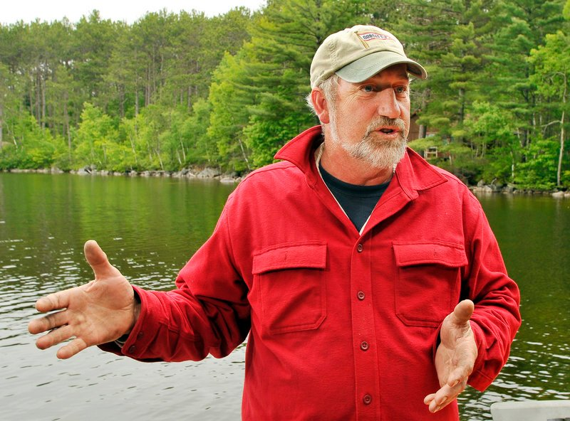 Dale Tobey, vice president of Grand Lake Stream Guides Association, opposes wind turbines on Bowers Mountain, below, which overlooks a multitude of remote lakes prized by fishermen seeking a wilderness experience. The 260-foot-tall meteorological tower visible here is considerably smaller than the wind turbines proposed for the site.
