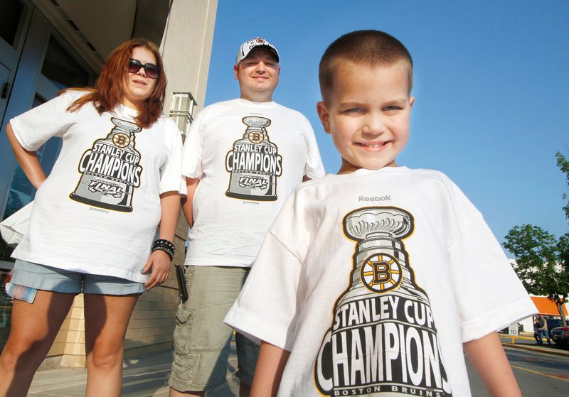 Debi Fields and Chris Lancey of Saco join their 5-year-old son, Aiden, in displaying Bruins pride outside the Maine Mall in South Portland on Thursday. The hockey fans said they bought the last two adult-sized shirts at Olympia Sports in Biddeford and came north to find championship caps.