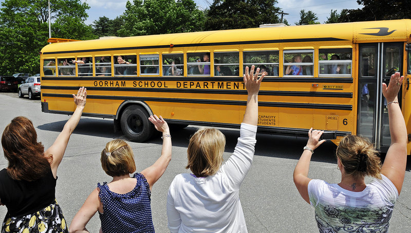 Teachers at White Rock Elementary School in Gorham line up to wave goodbye to students for the last time Friday. The K-2 school closed its doors for good and students will be relocated to a new K-5 school being built on Route 237.