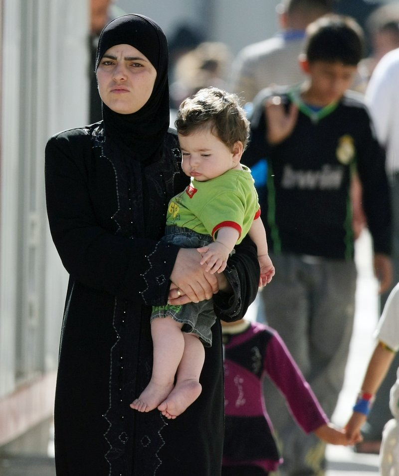 A Syrian refugee carries her child in a camp in Altinozu, Turkey, on Friday. Activists say the Syrian government has killed at least 1,400 people and detained 10,000.