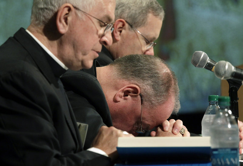 From left, Archbishops Joseph Kurtz and Timothy Dolan, and Monsignor David Malloy bow their heads in prayer as the U.S. Conference of Catholic Bishops' Spring General Assembly begins Wednesday in Bellevue, Wash.