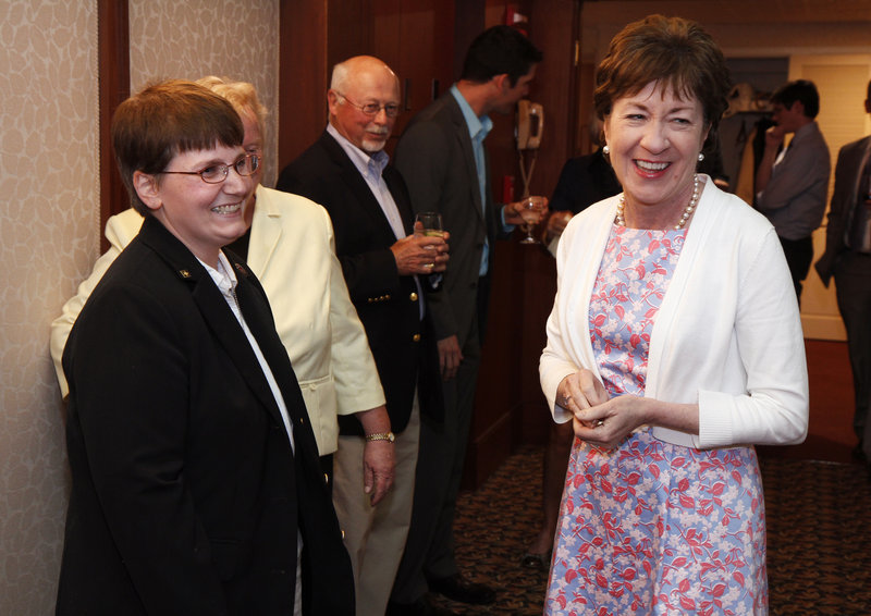 Sen. Susan Collins smiles Friday after receiving a ship's coin from Alicia Barnes at an EqualityMaine reception celebrating repeal of