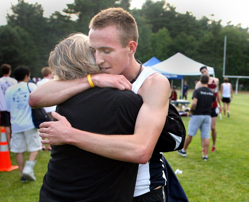 Riley Masters gets a hug from his mother, Alyce, after he placed second in the men's open mile during the Maine Distance Gala.
