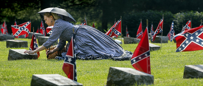 Civil War re-enactor Deby Fitzpatrick visits the grave of Sarah Newman, a woman she was portraying in Confederate Memorial Day ceremonies this month at the Confederate Memorial State Historic Site outside Higginsville, Mo.