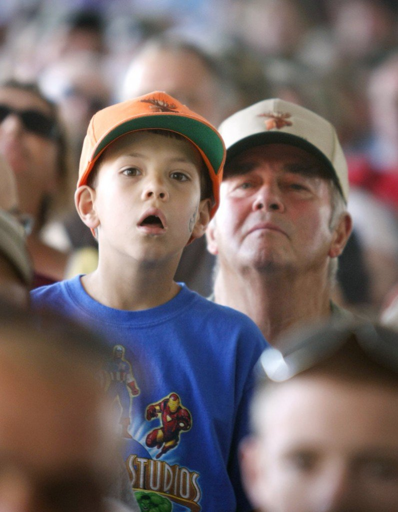 William Largey, 7, and his grandfather, Loren Largey, both of Gorham, keep a close eye on the video screen as names are called during the annual moose lottery Saturday.
