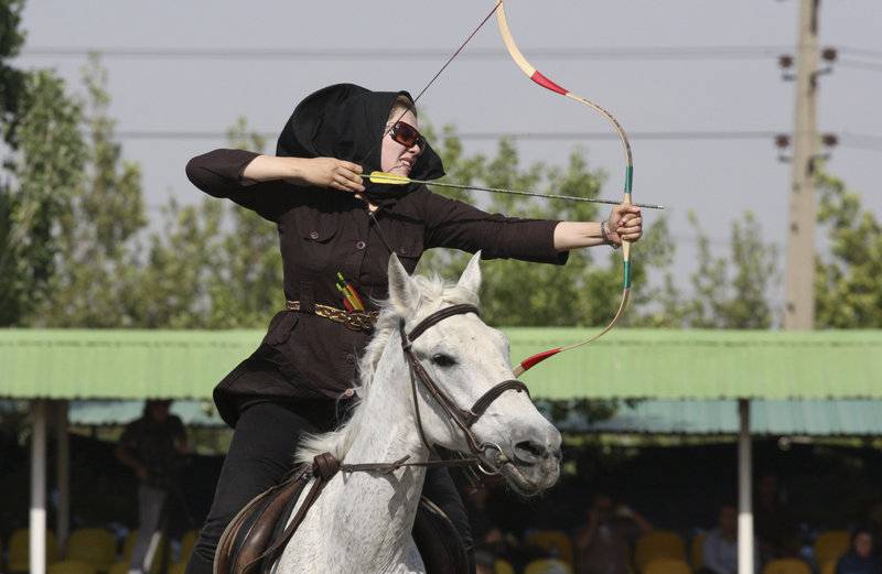 Shiva Mafakheri takes aim during at an archery event in Tehran, where 70,000 police officers have been deployed to enforce codes that ban cropped pants on women and earrings on men.