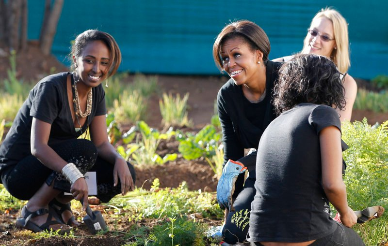 First lady Michelle Obama gardens as she participates in a community service project at Vhuthilo Community Center in Soweto township, Johannesburg, South Africa, Wednesday.