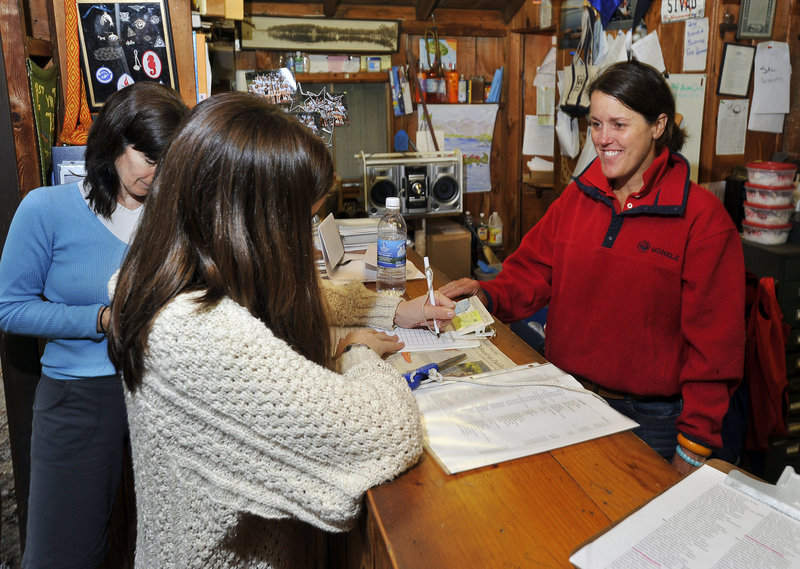 Ruth Keilty of Toronto, Canada, and her daughter Sloane Keilty, 14, check in Thursday with Quincy Van Winkle, right, owner/director with her husband of Wohelo Camps in Raymond.