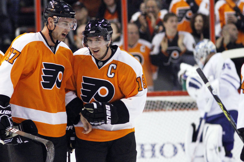 Jeff Carter, left, and Mike Richards are done celebrating as Flyers teammates after Philadelphia dealt them and their big contracts to Columbus and Los Angeles, respectively.