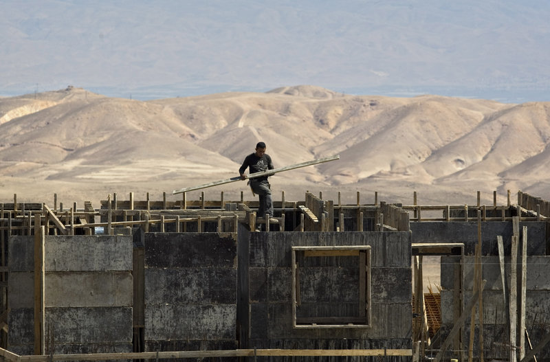 A Palestinian works at a construction site in the Jewish West Bank settlement of Maale Adumim. The Palestinians will drop their demand for an Israeli settlement construction freeze if Israel accepts a U.S. proposal for peace talks, a top official said Thursday.