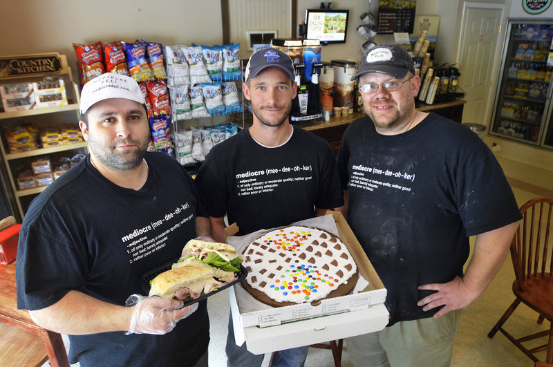 Aaron Plourde, Brian Bailey and Nate Legere of Mediocre Deli in Standish show a ham and Swiss sandwich and a jumbo whoopie pie they call a whooperoni. The deli serves breakfast, lunch and dinner, and takes orders online.