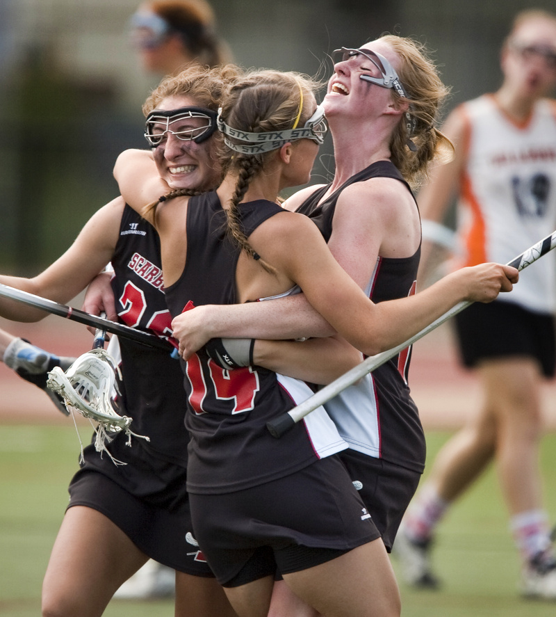 Mary Scott, center, celebrates with Ashley Ronzo, left, and Maggie Smith after scoring the goal that gave Scarborough a 12-8 lead against Brunswick on the way to a 13-11 victory in the Class A girls' lacrosse final.