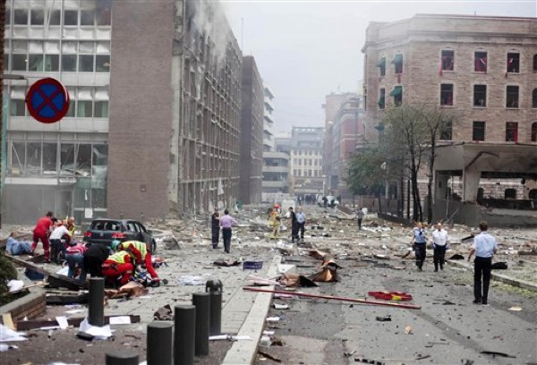 Victims receive treatment outside government buildings in the centre of Oslo, Friday July 22, 2011, following an explosion that tore open several buildings including the prime minister's office, shattering windows and covering the street with documents.(AP Photo/Fartein Rudjord)