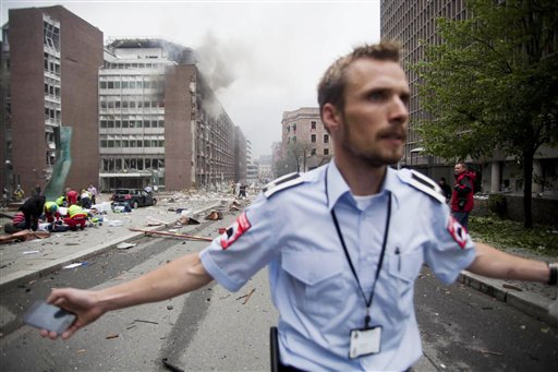 An official attempts to clear away spectators from buildings in the centre of Oslo, Friday July 22, 2010, following an explosion that tore open several buildings including the prime minister's office, shattering windows and covering the street with documents.(AP Photo/Fartein Rudjord) NORWAY OUT: