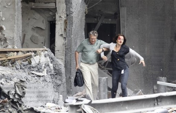 An injured woman is assisted from a damaged building in Oslo, Friday July 22, 2011, after an explosion rocked the capital. Terrorism ravaged long-peaceful Norway on Friday when a bomb ripped open buildings including the prime minister's office and a man dressed as a police officer opened fire at a nearby island youth camp. (AP Photo/Scanpix, Morten Holm) NORWAY OUT BNC