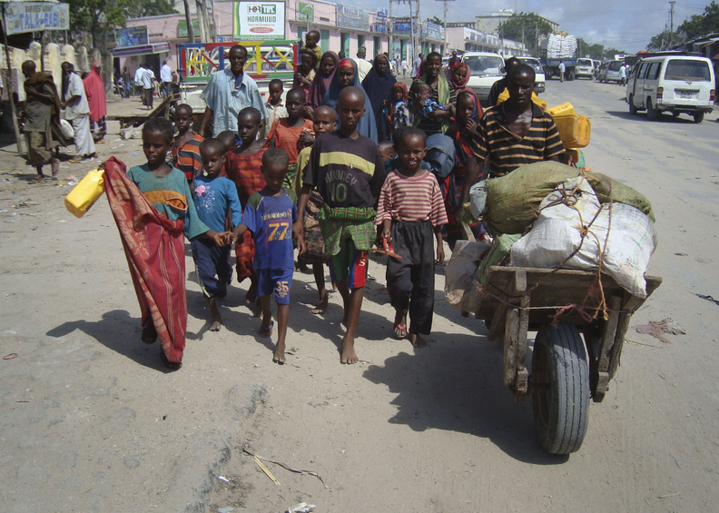 Refugees from southern Somalia carry their belongings as they make their way to a new camp for internally displaced people in Mogadishu on Thursday.