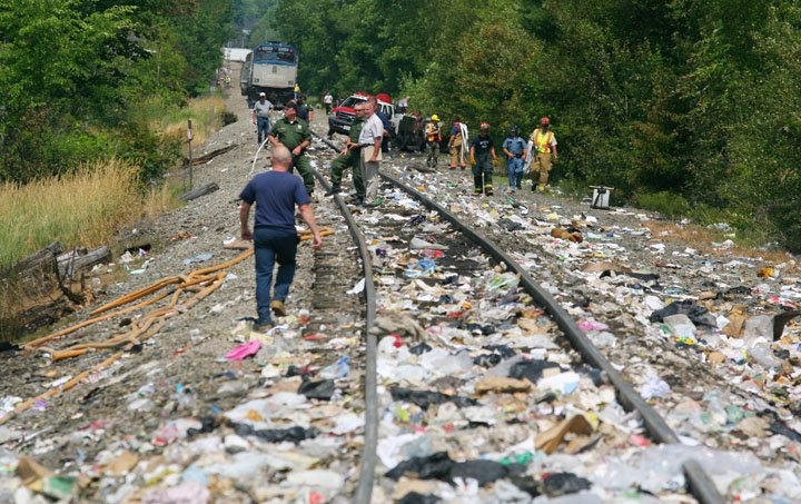 Emergency responders work amid trash strewn along the tracks in North Berwick where the Downeaster struck a trash-hauling tractor-trailer. The truck's driver was killed.