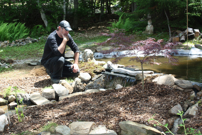 Island Micro Farm owner Mark Shain contemplates the rock placement around the farm's newly expanded water feature.